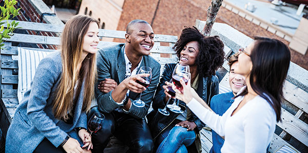 A group of Millennial friends drinking wine at a rooftop party.
