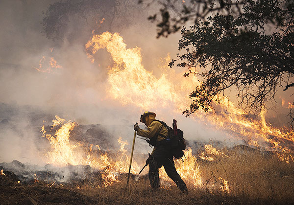 A firefighter battles the 2015 Valley Fire in California's Lake County.